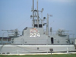 """The conning tower fairwater of U.S.S. Cod, in a photograph taken 6 September 2001 at her berth in Cleveland, Ohio. This is an excellent example of the """"covered wagon"""" bridge cutdown performed on many Gato class submarines to reduce the surface silhouette. The painted flags, representing wartime kills—and, in the case of the cocktail glass, a rescue—and the hull number would not have been present during wartime. Note the single-mount 40-mm guns on the forebridge and cigarette deck. Note also the SJ radar antenna behind the extended periscopes, and the retracted SD air warning radar on the aftermost mast, just forward of the after Target Bearing Transmitter. In a combat situation, this mast would be extended. Cod represents one of the finest restoration efforts to be found."""
